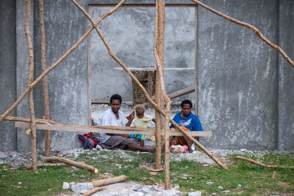 Two women and a child in the entrance to a half-constructed building in Lenakel, Tanna