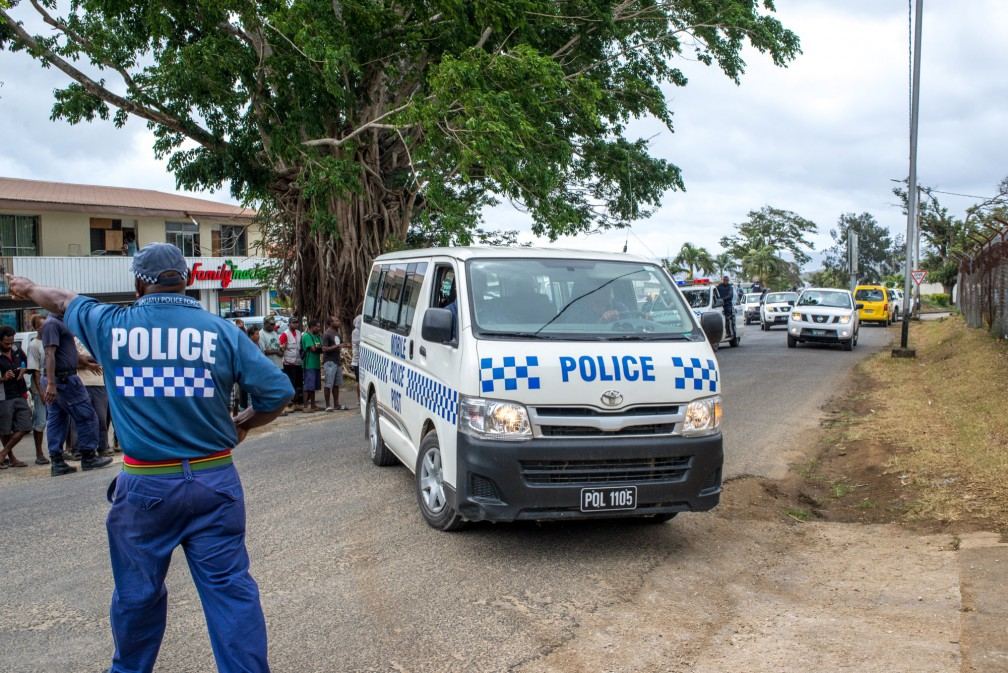 A senior police officer moves spectators back as 11 MPs and three of their lawyers are taken into custody following the issuing of a warrant on Friday.